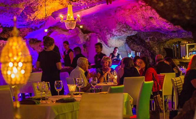 The main dining room is spacious and romantically lit by colored lights cast up the cave walls, ornate chandeliers, and classic furnishings / Photo: Facebook/Alux Restaurante